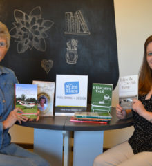 Carol Van Klompenburg and Sarah Purdy display memoirs that have been published by the Write Place.